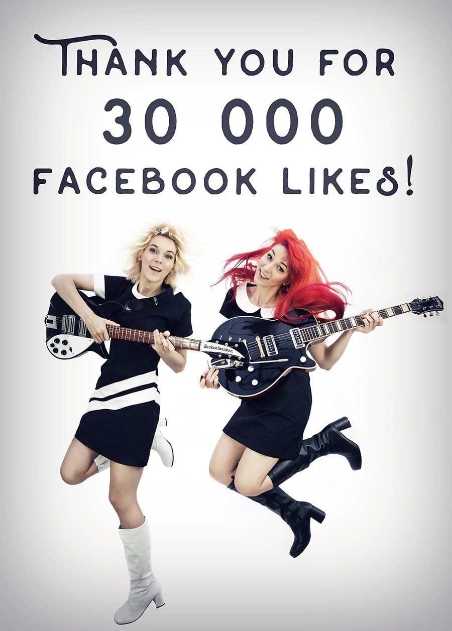 30 000 Facebook Likes - Mona and Lisa in black and white 60s Mods' dresses and boots, with their Rickenbacker and Gretsch guitars jumping with joy.