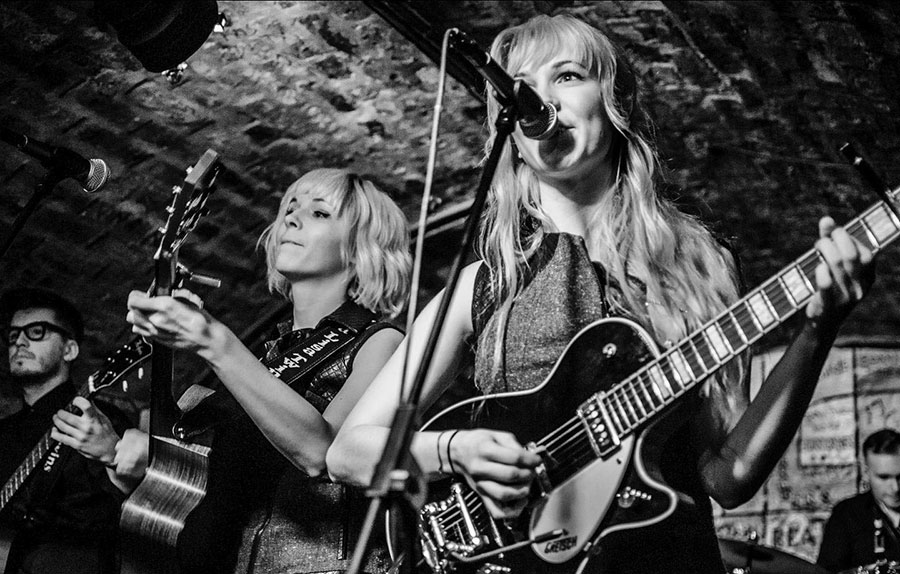 MonaLisa Twins at the Cavern Club 2014, black and white picture with Mona and Lisa in the foreground, on guitars and vocals