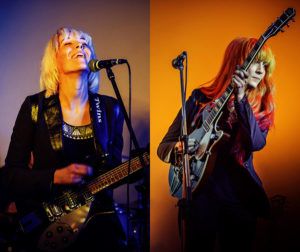 MonaLisa Twins Live Duo Photo, both with guitars on purple and orange backgrounds