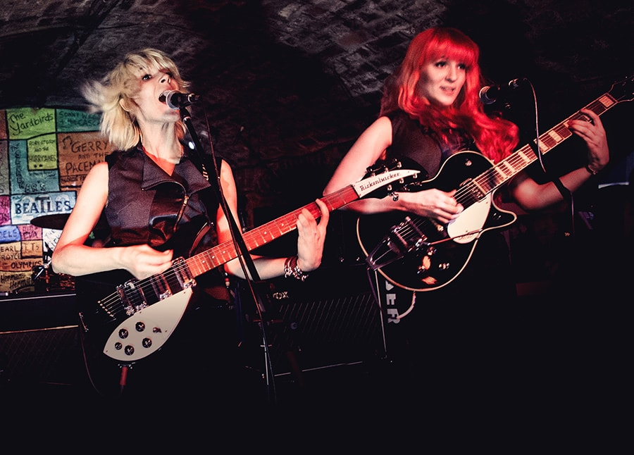 Mona and Lisa with guitars in front of the colorful backdrop of the world-known vaulted front stage of the Liverpool Cavern Club