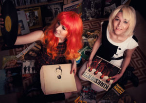 MonaLisa Twins sitting on the floor and sifting through an old 60's vinyl collection
